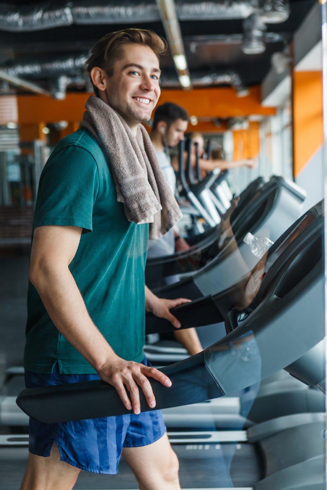 穿着绿色运动服在跑步机上运动的男性高清写真图