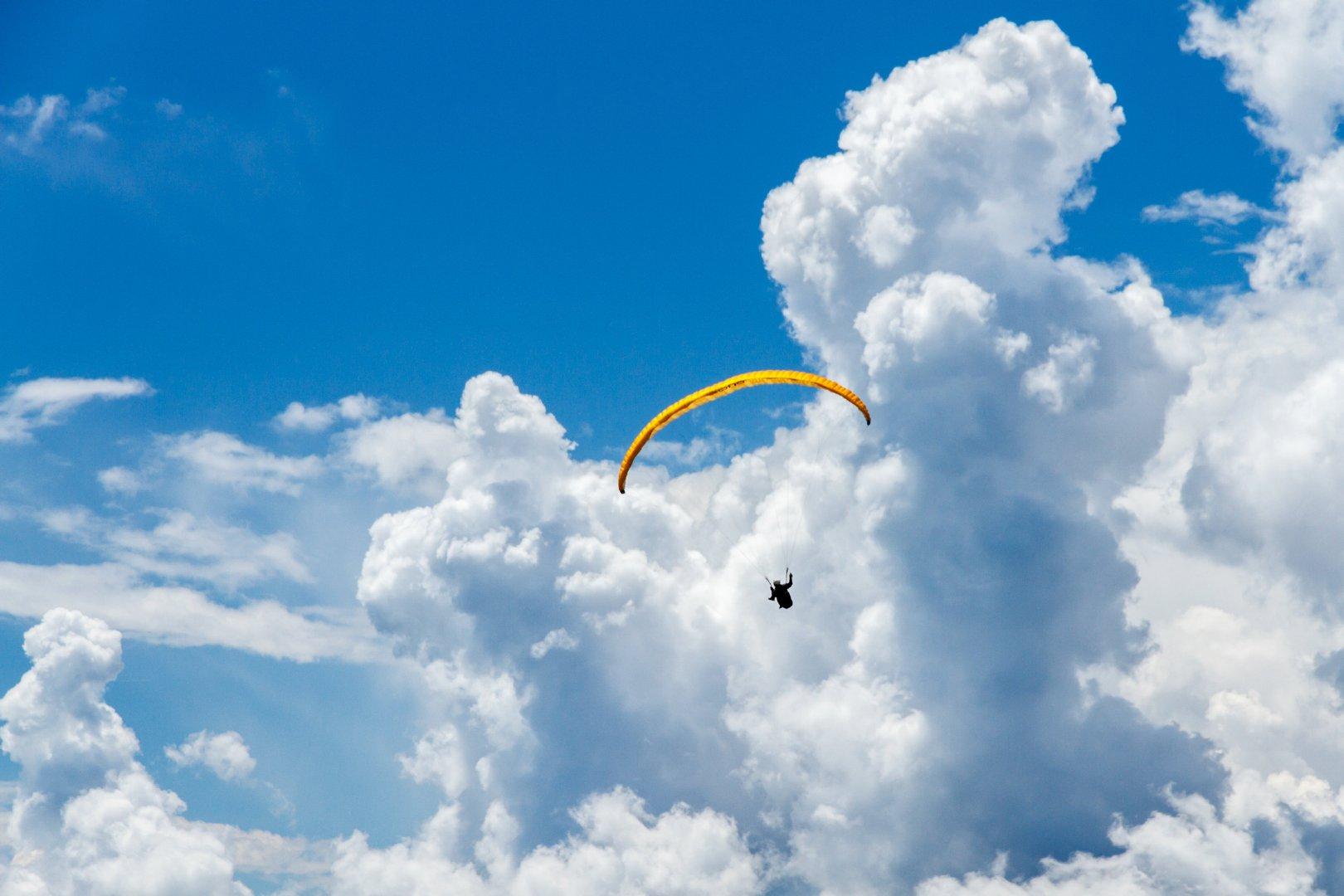 在蔚蓝天空中飞翔的滑翔伞高清特写