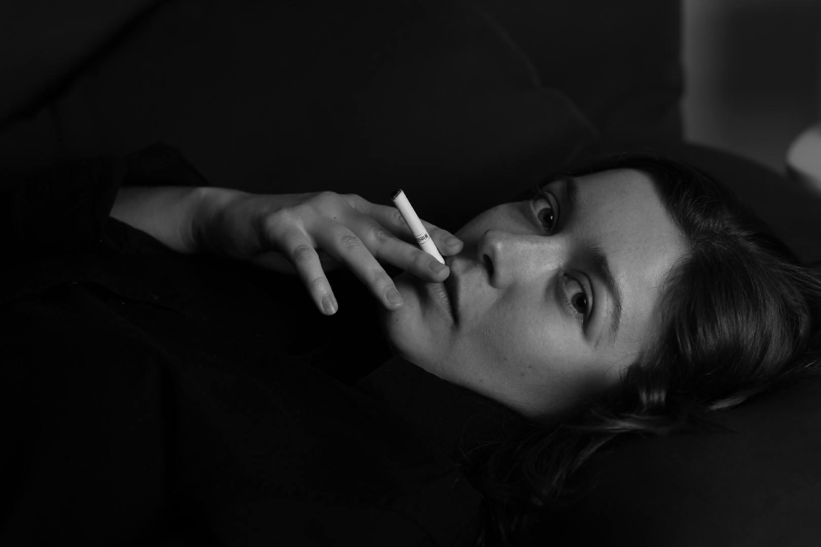 拿着烟吐出烟雾的美女摄影图片