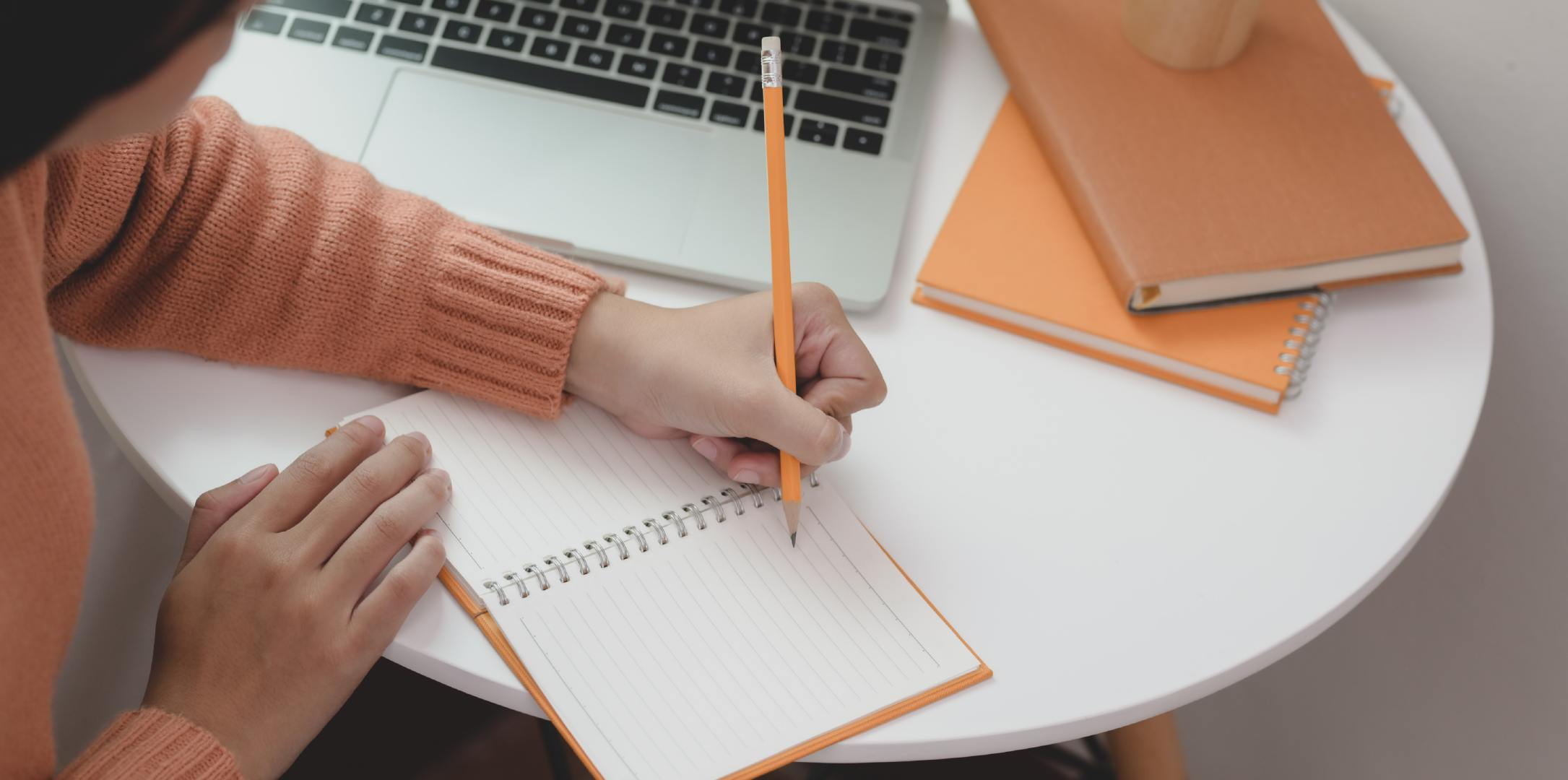 穿着棕色毛衣在办公桌上写字的白领摄影图片