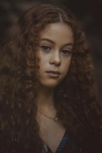 森林中棕色长卷发的女孩摄影图片