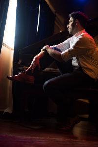 在钢琴旁沉思的白衬衫外国男子摄影图片