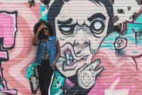 在炫酷的街头涂鸦前摆拍的人摄影图片