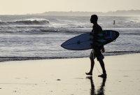 抱着冲浪板的人走在湿润沙滩上电脑壁纸